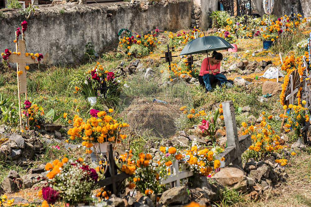 A woman sits by the grave of a relative surrounded by marigold decorations during the Day of the Dead festival November 2, 2017 in Ihuatzio, Michoacan, Mexico.  The festival has been celebrated since the Aztec empire celebrates ancestors and deceased loved ones.