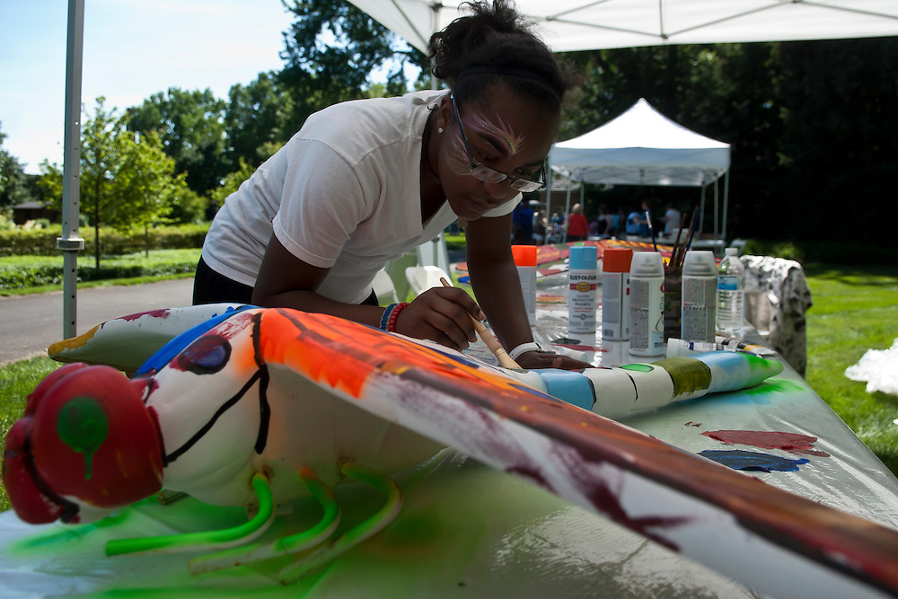 Lathan Goumas | MLive.com..DeShawna Psalms, of Flint, paints a dragon fly statute during a Summer Fun Day event at the Applewood Estate in Flint, Mich. on Thursday June 14, 2012.