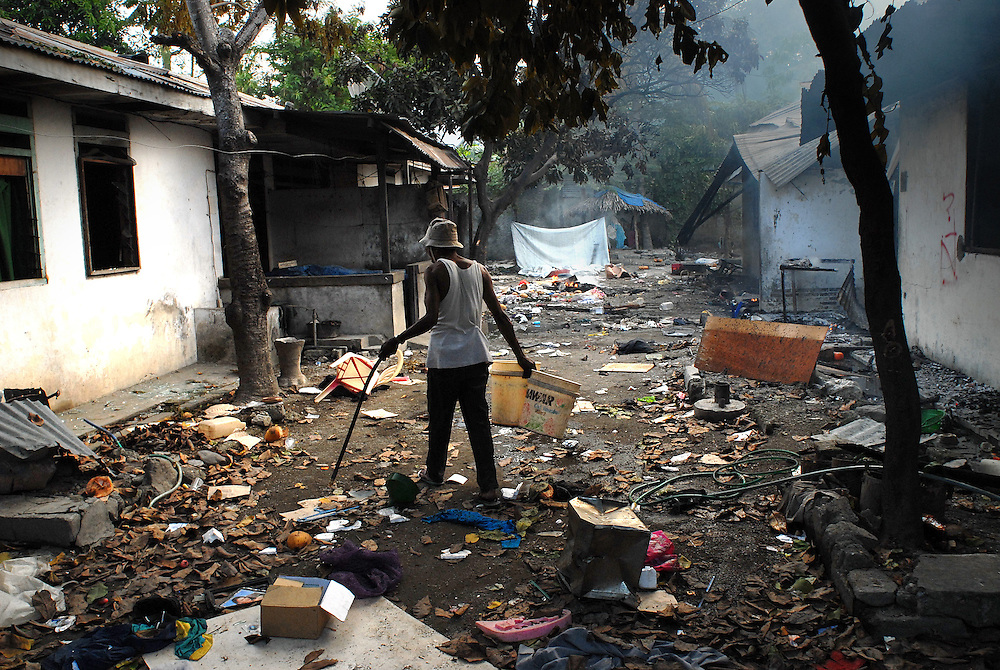 A man sifts through the ruins of his neighbourhood in Calico, near the Old Market area of Dili, as continual violence, looting and arson disrupt Dili. There is some confusion in Dili as to whether the violence is the result of ethnic tensions, or localised gang violence.
