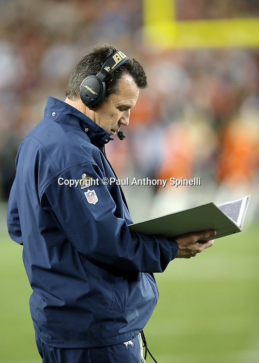 Denver Broncos head coach Gary Kubiak checks out formation photographs on the sideline during the NFL Super Bowl 50 football game against the Carolina Panthers on Sunday, Feb. 7, 2016 in Santa Clara, Calif. The Broncos won the game 24-10. (©Paul Anthony Spinelli)