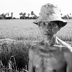 A Khmer farmer with chest tattoos stands in his rice field near Battambang, Cambodia.