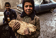 Afghanistan. the street of the old city of  Kabul  Afghanistan   / a child with some bread /  les ruelles du  vieux kaboul medieval  à Kaboul  Kaboul  Afghanistan  /  56808
