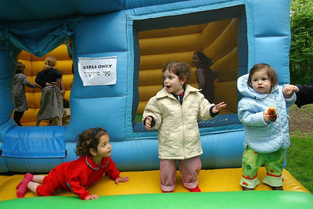 Young Orthodox Jewish girls play on a bouncy castle at a community event in Allen Gardens, Stamford Hill to celebrate Lag B'Omer. Women and Men are kept separate at all times including children, they have separate play area's. Lag B'Omer is the holiday celebrating the thirty-third day of the (counting of the) Omer. Jews celebrate it as the day when the plague that killed 24,000 people ended in the holy land (according to the Babylonian Talmud). Other sources say the plague was actually the Roman occupation and the 24,000 people died in the second Jewish - Roman war  (Bar Kokhba revolt of the first century).  Bonfires (used as signals in wartime) are symbolically lit to commemorate the holiday of Lag'B'Omer.