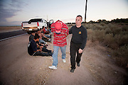 17 MAY 2006 - GILA BEND, AZ: Maricopa County Deputy Jason Schweizer, RIGHT, walks Ruben Tiscareno, from San Luis, AZ, to a waiting patrol car after he arrested Tiscareno for a driving a pick up truck full of undocumented immigrants on Old King's Highway north of Gila Bend Wednesday morning. PHOTO BY JACK KURTZ