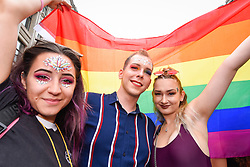 © Licensed to London News Pictures. 06/07/2019. LONDON, UK.  People in the crowd celebrate with a rainbow flag. Tens of thousands of visitors, many wearing eye-catching costumes, gather to watch and take part in the annual Pride in London Parade, the largest celebration of the LGBT+ community in the UK.  This year's event also celebrates 50 years since the birth of the modern LGBT+ rights movement. Photo credit: Stephen Chung/LNP