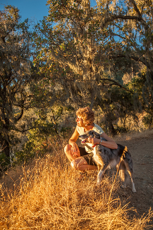Mitzi Mishler with her dog Molly at sunset near the start of the Oak Hill Trail in Calistoga