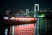 """Customers enjoy the above deck views of the Odaiba district from one of Harumiya Co.'s """"yakata-bune"""" pleasure boats in Tokyo Bay, Japan on 31 August  2010. Photographer: Robert Gilhooly"""