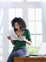 Woman reading paper document sitting on desk