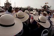 Mikoshi supporters in wide-brimmed hats watch as mikoshi are carried into the sea during the Hamaorisai Matsuri that takes place on Southern Beach in Chigasaki, near Tokyo, Kanagawa, Japan Monday July 18th 2011. The festivals marks the celebration of Marine Day and the rescuing of a divine image that was washed ashore in the area. Over thirty Mikoshi or portable shrines are carried through the night from surrounding shrines to arrive on the beach for sunrise. There they are blessed and then carried into the surf to purify them.