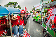 "10 DECEMBER 2012 - BANGKOK, THAILAND:   A convoy of Red Shirt ""tuk-tuks"" (three wheeled taxis) go to the Pheu Thai offices on Petchaburi Road in Bangkok Monday. The Thai government announced on Monday, which is Constitution Day in Thailand, that will speed up its campaign to write a new charter. December 10 marks passage of the first permanent constitution in 1932 and Thailand's transition from an absolute monarchy to a constitutional monarchy. Several thousand ""Red Shirts,"" supporters of ousted and exiled Prime Minister Thaksin Shinawatra, motorcaded through the city, stopping at government offices and the offices of the Pheu Thai ruling party to present demands for a new charter.       PHOTO BY JACK KURTZ"