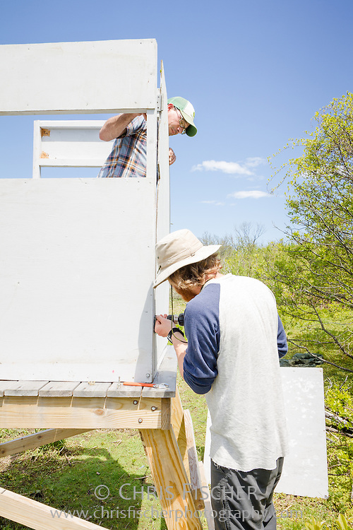 Volunteer Robby Lambert (top) holds the door in place while field station supervisor John Gorey attaches the door to a new wildlife viewing blind beside the interior pond on Stratton Island, Maine.