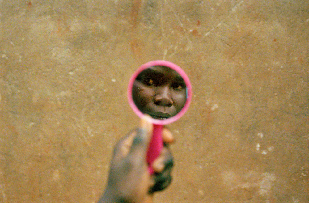 Facing the future Uganda's child soldiers return home. ..A boy at the rehabilitation centre walks around looking at himself in a mirror with his mirror, all the former child soldiers are given a hygine kit when they arrive. A new priced possesion.