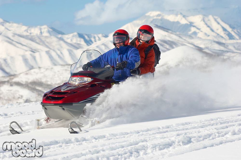 Couple Snowmobiling with Mountains in Background