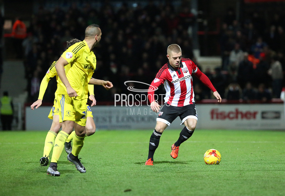 Brentford defender Jake Bidwell surrounded by two Boro players during the Sky Bet Championship match between Brentford and Middlesbrough at Griffin Park, London, England on 12 January 2016. Photo by Matthew Redman.