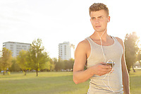 Young jogger looking away while listening music through cell phone in park