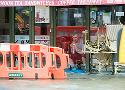 © Licensed to London News Pictures. 06/10/2014. Twickenham, UK. A local shop worker looks out of the flooded premises.  Firefighters help to contain a mains water pipe which has burst in King Street Twickenham today 6th October 2014. It appears that workmen working in the area have used a JCB digger to stem the flow. Many local shops and businesses have been flooded.   Photo credit : Stephen Simpson/LNP