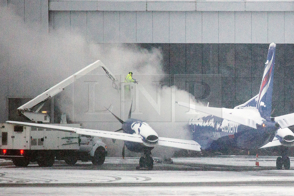 © Licensed to London News Pictures. 27/02/2018. Leeds UK. An aircraft is blasted with high pressure water to clear away snow this morning at Englands highest airport Leeds Bradford International in Yorkshire. Photo credit: Andrew McCaren/LNP