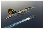 F-18E over aircraft carrier, aerial view