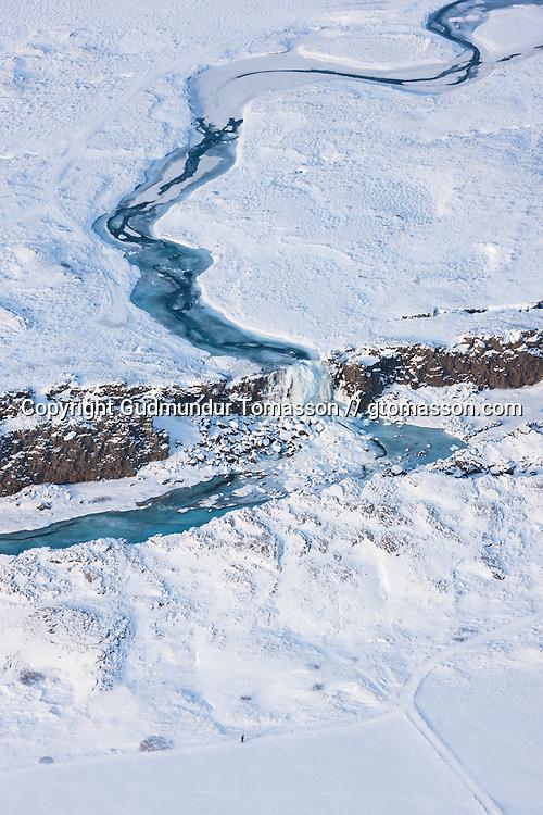 The waterfall Öxarárfoss frozen at winter at Þingvellir national park, Iceland.