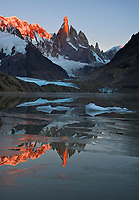 One of the world's most majestic granite spires, the unforgettable Mount Cerro Torre in Patagonia, Argentina, is clothed in intense, red alpen glow, its reflection broken by thin layers of ice which formed during the cold, windless night.