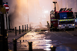 © Licensed to London News Pictures . 13/07/2013 . Manchester , UK . Fire crews work to quell the fire . A fire fighter is dead and two 15 year old girls are under arrest on suspicion of manslaughter after a blaze in Manchester yesterday (Saturday 13th July) . More than 60 fire fighters tackled a blaze at Paul's Hair World on Oldham Street in Manchester City Centre late in to the night (Saturday 13th July 2013) . Twelve crews from four stations were deployed . Several streets in a block in the city centre are sealed off . Photo credit : Joel Goodman/LNP