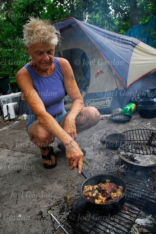 Homeless elderly white woman cooking in the Macon-Delta a camp of homeless people living in the woods of Orlando. They are called the tree people by other homeless street people.