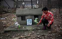 Chinese village Dong Aicun of Dongtan Village adjust flowers by the grave of her mother Huang Hongmei who died from throat cancer last year in Zekou Town, Qianjiang City of Hubei Province, China 15 January 2013. While the heavy smog in Beijing and much of northern China in recent days have caused alarm among residents and renewed scrutiny on the pollution woes of the country, villagers in a small town of Hubei Province have been grappling with severe air, water and noise pollution on a daily basis over the past two years. China's Xinhua news reported 04 January 2013 that more than 60 cancer deaths in various villages of Zekou Town has been caused by the heavy pollution from the chemical industry park nearby. About 20 or more chemical plants built around the villages of Dongtan, Xiangnan, Zhoutan, Sunguai, Qingnian and others over the past two years has created huge increases in noise, air and water pollution. Many villagers complained of intensifying respiratory, heart, skin and circulatory illnesses caused by the pollution and a large spike in cancer diagnoses and deaths since the factories were built. .