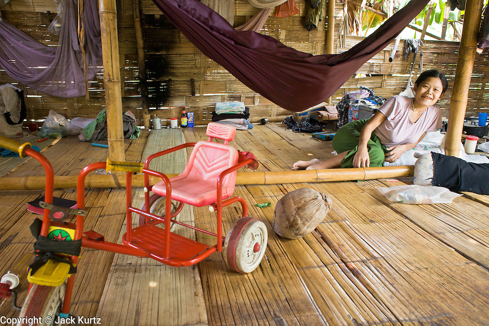 18 FEBRUARY 2008 -- BONG TI, KANCHANABURI, THAILAND: A baby sleeps in a hammock while her mother sits nearby in a Karen refugee village near the Bamboo School in Bong Ti, Thailand, about 40 miles from the provincial capital of Kanchanaburi. Sixty three children, most members of the Karen hilltribe, a persecuted ethnic minority in Burma, live at the school under the care of Catherine Riley-Bryan, whom the locals call MomoCat (Momo is the Karen hilltribe word for mother). She provides housing, food and medical care for the kids and helps them get enrolled in nearby Thai public schools. Her compound is about a half mile from the Thai-Burma border. She also helps nearby Karen refugee villages by digging water wells for them and providing medical care. Thai authorities have allowed the refugees to set up the village very close to the border but the villagers are not allowed to own land in Thailand and they can't legally leave the area to get jobs in Thailand.    Photo by Jack Kurtz