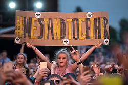 "© Licensed to London News Pictures . 27/05/2017 . Manchester , UK . A woman holds up a hand painted sign , with Manchester bee stickers , reading "" WE STAND TOGETHER "" during the Courteeners' set . Manchester music line up , featuring Courteeners , Charlatans , Blossoms and Cabbage , at the Emirates Old Trafford Stadium . Photo credit : Joel Goodman/LNP"