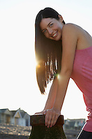 Young woman leaning on metal stump on beach