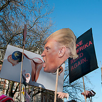 London UK. January 21st 2017.An estimated 100,000 protesters took part in a Women's March from the US Embassy in Grosvenor Square to Trafalgar Square as part of an international campaign on the first full day of Donald Trump's Presidency of the United States.  A group hold Trump's head on a stick, his hands and a placard showing a woman's reproductive organs, referencing  fears that Trump will overturn the Affordable Care Act and thus threaten reproductive health care. There is also a placard saying 'Make Amerika read again'.