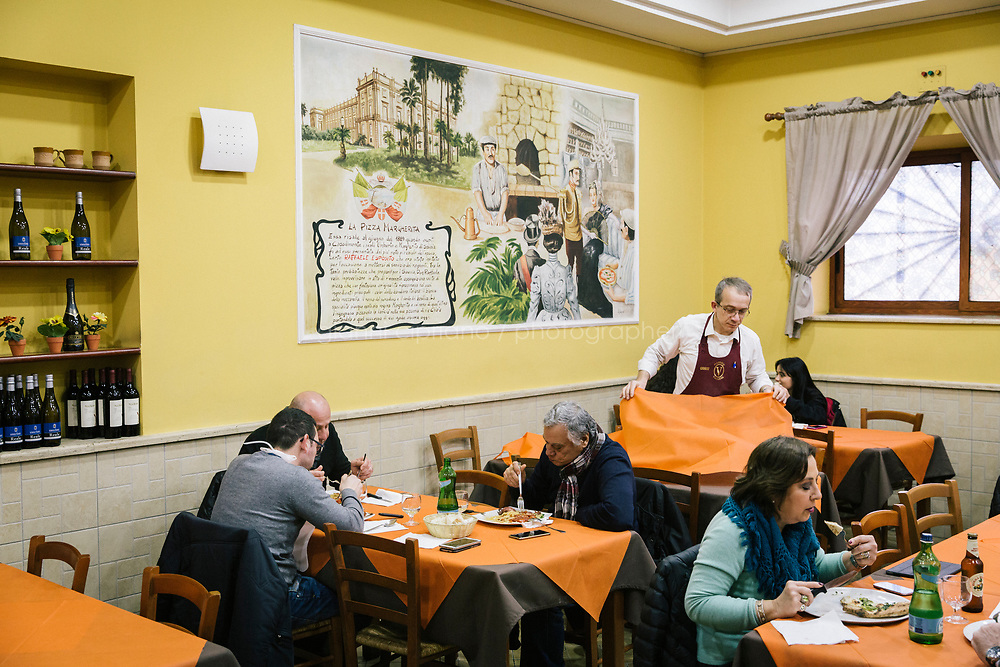 NAPLES, ITALY - 20 MARCH 2018: Customers have lunch at the Pizzeria e Trattoria Vigliena in Naples, Italy, on March 20th 2018.<br /> <br /> Pizzeria e Trattoria Vigliena is a restaurant outside of the city center and adjacent to the port. At lunch, the place is packed with workers from the docks and ship owners and workers from the recently built Marina Vigliena.<br /> <br /> The restaurant is owned by Raffaele Esposito, Concetta&rsquo;s son and the third generation of a family of chefs who founded this restaurant in the middle of the 20th century