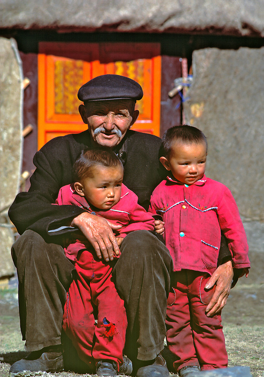 A grandfather hugs his two grandsons at the South Pasture, Urumqi, Xinjiang, China.