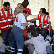"Tenerife / Los Cristianos June 7, 2006 - would-be immigrants rest in a Red Cross tent after arriving at the canary islands - A fishing boat called ""Cayucos"" by the inhabitants of the island, with 85 would-be immigrants from West Africa intercepted by Spanish police of the coast of Tenerife in the Canary Islands are seen in an open wooden fishing vessel as they approach the port of Los Cristianos. They arrived on June, carrying 85 would-be immigrants, in the archipelago which has received more than 7,000 Africans so far this year, more than half to the tourist resort island of Tenerife. At least 1,000 more are believed to have died trying to make the sea crossing, mostly in small fishing boats"