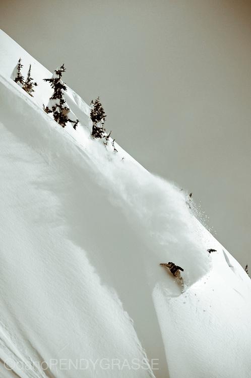 Professional snowboarder Chris Wimbles sprays some light winter snow in the Coast Mountain Range of British Columbia.