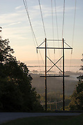 Powerlines running down a hill into a foggy valley.