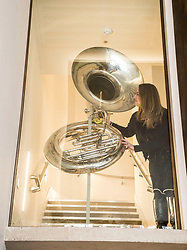 Learning &amp; Engagement Curator Sarah Deters cleans a 1930's sousaphone now on display above the entrance to  the newly-refurbished St Cecilia's Hall, which has just undergone a 2 year, &pound;6.5 million refurbishment which will see more of the University of Edinburgh's musical instrument collection on display to the public.<br /> <br /> &copy; Dave Johnston/ EEm