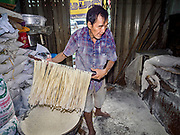 "29 DECEMBER 2018 - BANGKOK, THAILAND: A man drags longevity noodles through flour during the noodle's drying process in his family shophouse. The family has been making traditional ""mee sua"" noodles, also called ""longevity noodles"" for three generations in their home in central Bangkok. They use a recipe brought to Thailand from China. Longevity noodles are thought to contribute to a long and healthy life and  are served on special occasions, especially Chinese New Year, which is February 4, 2019. These noodles were being made for Chinese New Year.  PHOTO BY JACK KURTZ"