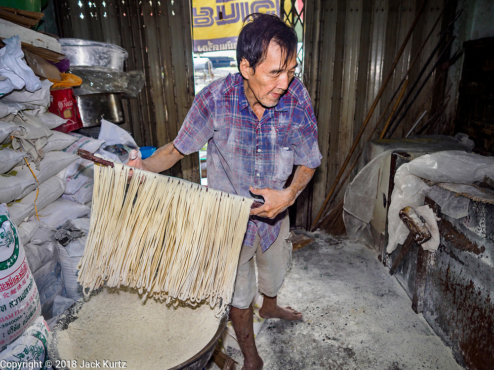 """29 DECEMBER 2018 - BANGKOK, THAILAND: A man drags longevity noodles through flour during the noodle's drying process in his family shophouse. The family has been making traditional """"mee sua"""" noodles, also called """"longevity noodles"""" for three generations in their home in central Bangkok. They use a recipe brought to Thailand from China. Longevity noodles are thought to contribute to a long and healthy life and  are served on special occasions, especially Chinese New Year, which is February 4, 2019. These noodles were being made for Chinese New Year.  PHOTO BY JACK KURTZ"""