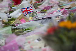 © Licensed to London News Pictures . 27/03/2017 . London , UK . A woman takes a photograph of flowers and tributes in Parliament Square opposite Parliament in Westminster in response to Khalid Masood's terrorist attack and the killing of PC Keith Palmer . Photo credit: Joel Goodman/LNP