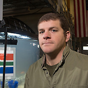 Corey Heim, Chief Operating Officer of DryCase, poses for a portrait with a waterproof iPad cover displaying the flag of South Africa submerged in an aquarium at the company's warehouse in Wilmington, N.C. Wednesday January 22, 2014. (Jason A. Frizzelle)