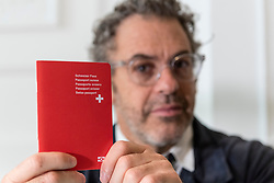 "© Licensed to London News Pictures. 05/10/2018. LONDON, UK. Tom Sachs issues a passport. Preview of ""Swiss Passport Office"" by American artist Tom Sachs at Galerie Thaddaeus Ropac in Mayfair.  To coincide with Frieze Week, the gallery will remain open for 24 hours from 6pm 5 October to 6pm 7 October for the issuing of serial-numbered Tom Sachs Swiss passports for visitors.  The installation reflects the concerns relating to Brexit, Syria and Donald Trump's immigration policies and challenges the notion of global citizenship.  Photo credit: Stephen Chung/LNP"