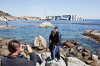 GIGLIO (GR), ITALY - 9 APRIL, 2012: A young couple poses for a snapshot in front of the capsized cruise ship in Giglio. Giglio, a Tuscan island famous for its pristine waters and quiet living style, faces the challenges of starting a tourist season with a 225,000-tonne ship stuck at the entrance of its tiny port. Months after the Costa Concordia shipwreck, the Tuscany Region and Ministry for Tourism financed a 50,000-euro promotional campaign to encourage visitors to go to Giglio for the summer, while islanders are creating new walking paths and wine tasting tours to diversify their offer, trying to take advantage of the popularity that the tiny island has gained globally last January. The new attraction on Giglio has already caused an increase in the number of tourists who go to the island just for one day. <br /> <br /> Ph. Gianni Cipriano for The New York Times
