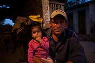 A cowboy and his daughter look towards the camera after a days work in the Bolivian Amazon.