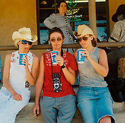 Three women drinking pepsi two wearing cowboy hats one with a camera USA