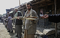 20011019-BAZARAK, AFGHANISTAN: People carry dishes after their pray in Bazarak during the prayer and mourning day, the 40th day of the death of opposition commander Ahmad Shah Masood, 19 October, 2001.