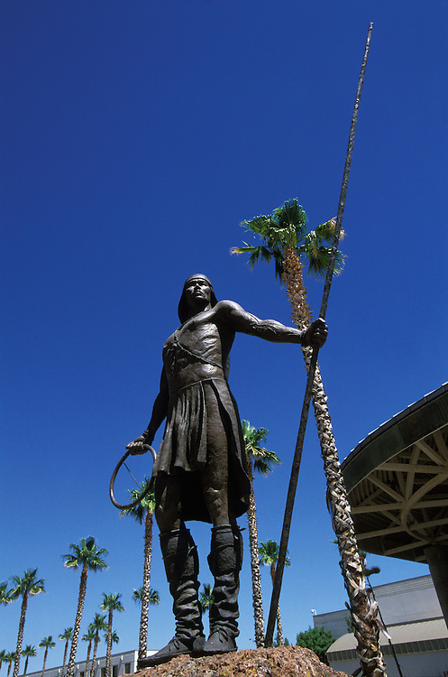 A statue of an Apache Indian in front of the Apache Gold Casino on the San Carlos Apache Indian Reservation in Arizona, USA. June 2004. In his hands he holds a staff and a ring used in the traditional hoop game.
