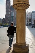 A man smokes beneath Renaissance arches of the Cloth Hall and one of the towers of the Church of St Mary on Rynek Glowny market square, on 23rd September 2019, in Krakow, Malopolska, Poland.