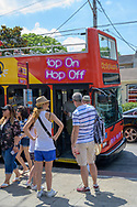 New Orleans, LA, USA -- May 26, 2019.  A Hop-on Hop-off bus in New Orleans arrives at the stop to pick up waiting passengers.