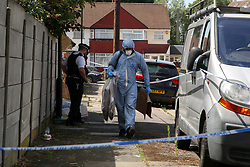 © Licensed to London News Pictures. 17/07/2020. London, UK. A forensic officer with evidence bags on Lytton Avenue, Enfield, in north London as police launch a murder investigation following the death of a man in his 30s. Police were called at 04:45hrs early this morning, to a report of four men fighting in Lytton Avenue, Enfield and a man being put into a vehicle. Later the victim died from a single stab wound in North Middlesex Hospital. Three men, no further details, have been arrested on suspicion of murder; all remain in custody. Photo credit: Dinendra Haria/LNP